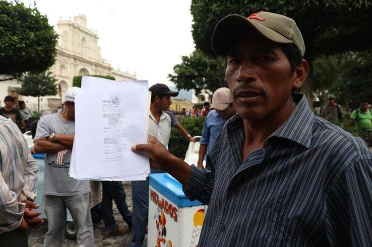 Un vendedor de helados de Antigua Guatemala muestra documento sobre multa impuesta por la comuna. (Foto Prensa Libre Renato Melgar)