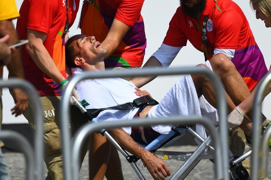 Un grupo de médicos atiende al atleta. (Foto Prensa Libre: AFP)