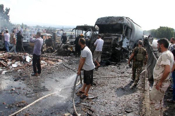 Varios vehículos quemados en el lugar de atentado en Tartus, Siria. (AP).