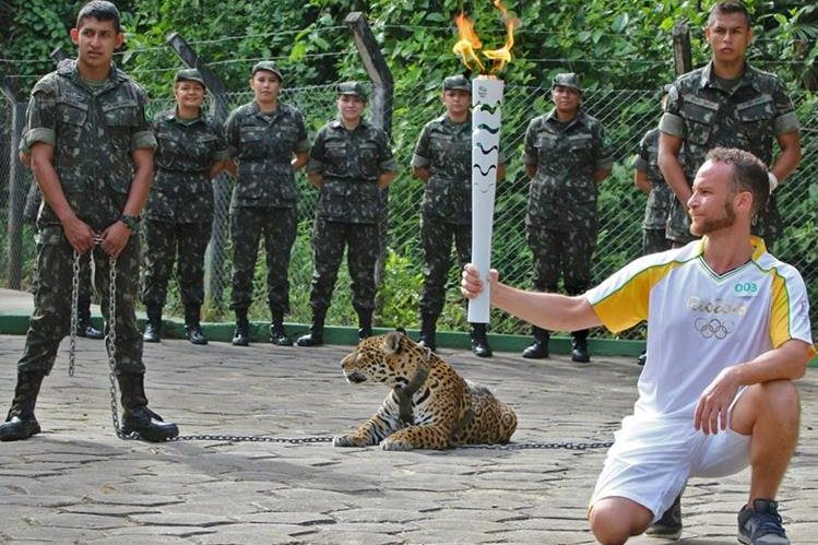 """Un atleta sostiene una antorcha mientras el jaguar """"Juma"""" es exhibido durante el acto. (Foto Prensa Libre: AFP)."""