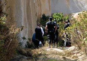 Fiscales del MP inspeccionan lugar donde encontraron el cadáver de un migrante hondureño, en Concepción Chiquirichapa, Quetzaltenango. (Foto Prensa Libre: Carlos Ventura)