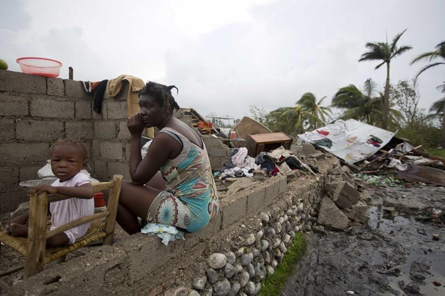 Victor Farah y su hija observan la destrucción que dejó en su hogar el huracán Matthew. Foto Prensa Libre. AP).