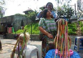 Una de las mujeres procedentes de Izabal elabora trenzas en el cabello de una joven. (Foto Prensa Libre: Álvaro Interiano).