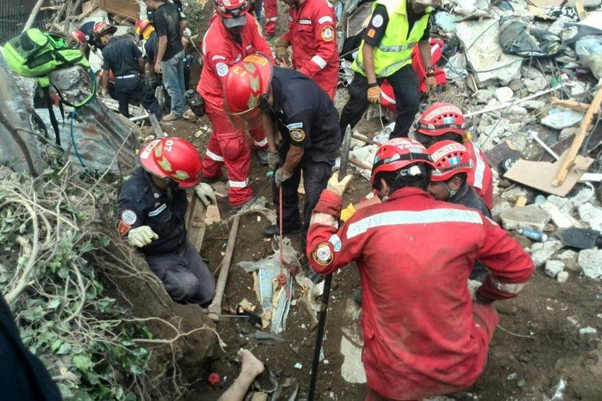 Socorristas rescatan cuerpos de personas entre los escombros de las paredes. (Foto Prensa Libre: Edwin Bercián)