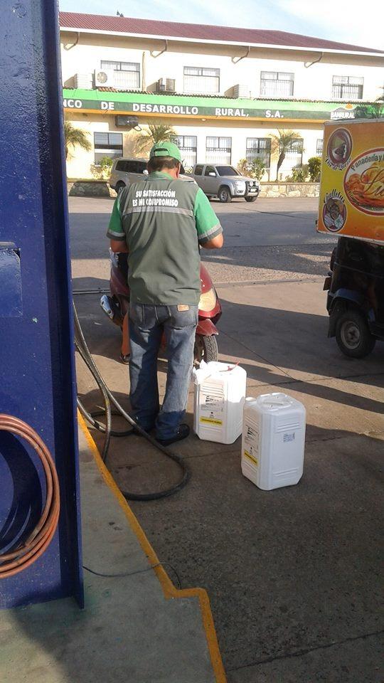 Un automovilista llena recipientes plásticos con combustible en gasolinera de Morales, Izabal. (Foto Prensa Libre: Dony Stewart)