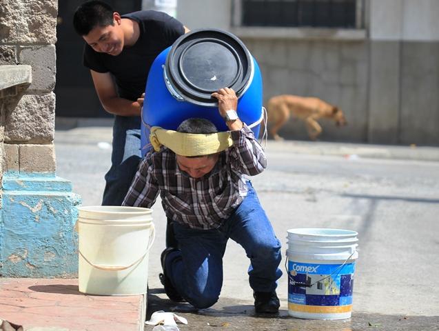 Alfredo Tul Caal con ayuda de su hijo Byron Otoniel, llevan agua a sus vivienda en la colonia San Julián, Nueva Chinautla, Guatemala. Por vivir en zona roja, el camión cisterna no llega hasta su vivienda. (Foto Prensa Libre: Esbin García)