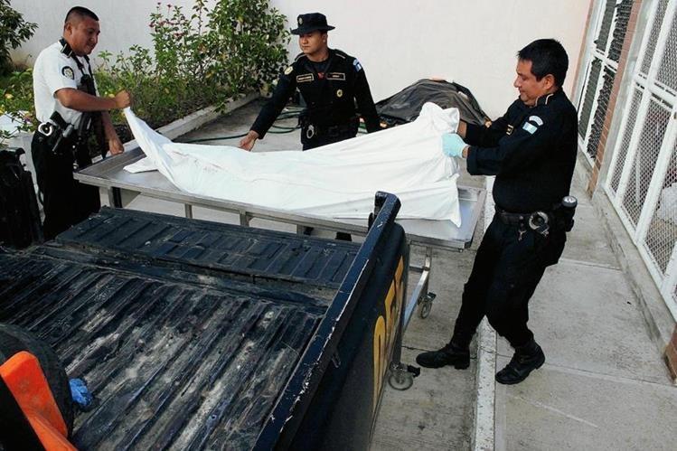 Empleados de morgue y agentes policiales trasladan cadáver de hombre, en Dolores, Petén. (Foto Prensa Libre: Walfredo Obando)