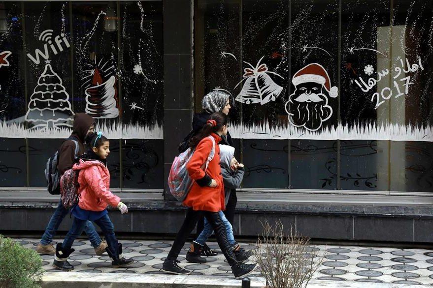 Una mujer y su hija caminan frente a negocios que lucen desolados. (Foto Prensa Libre: AFP).