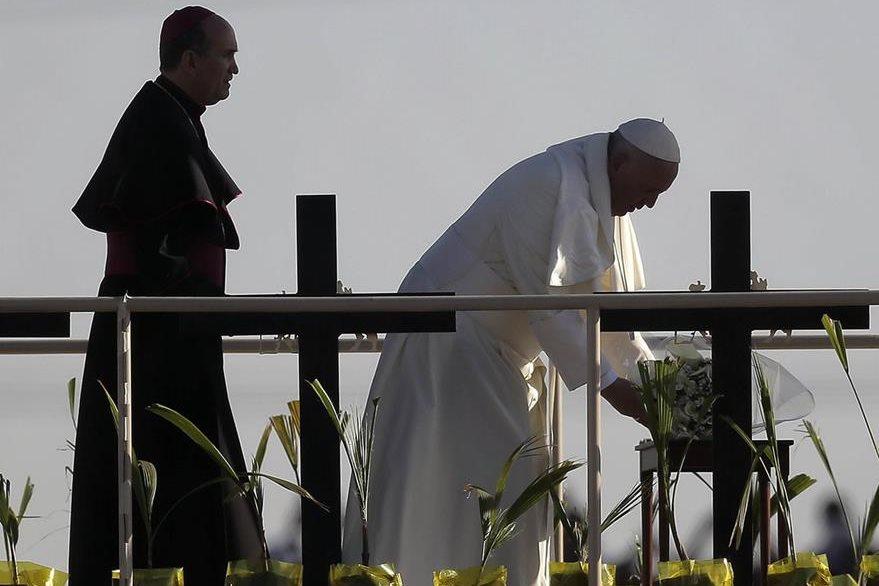 El papa Francisco coloca una ofrenda floral por los inmigrantes fallecidos. (Foto Prensa Libre: AP).