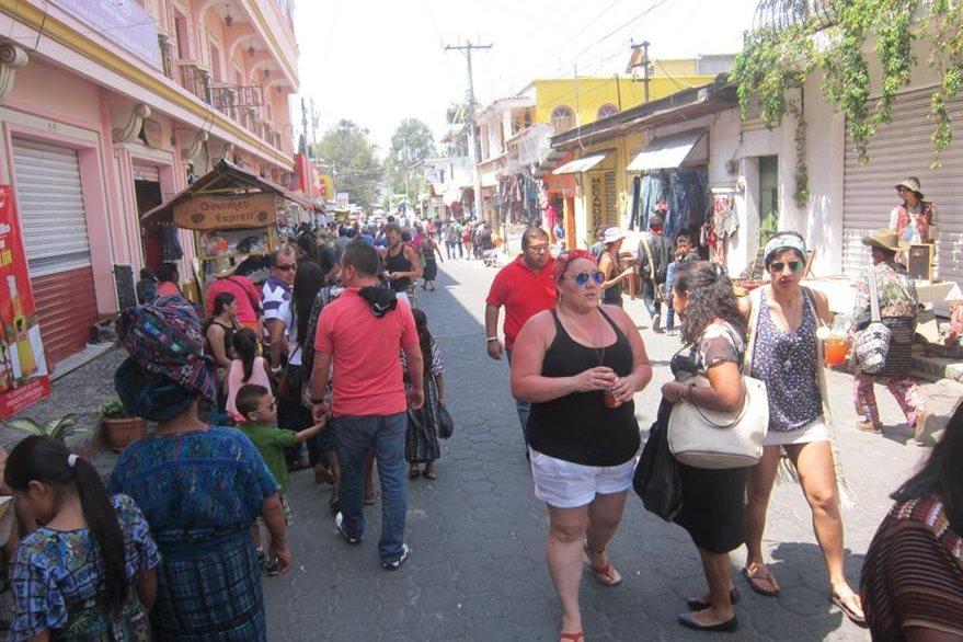 Turistas caminan por la Calle Santander, en Panajachel, antes de regresar a sus lugares de residencia. (Foto Prensa Libre: Ángel Julajuj)