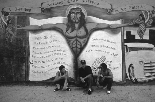 Departamento de Policía de Los Ángeles estima que la ciudad tiene unas 450 bandas con 45.000 integrantes. Tomada un año antes de los disturbios de Rodney King de 1992 que sacudieron a Los Ángeles, la fotografía muestra a pandilleros frente a un mural en el este de la ciudad. WALTER LEONARDI