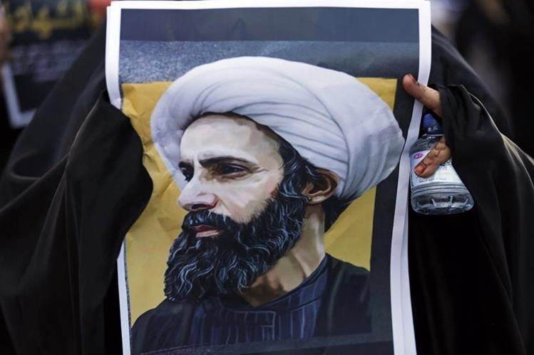 Un maniestante en Baréin sostiene una imagen del fallecido líder chií saudí, Sheikh Nimr al- Nimr. (Foto Prensa Libre: AP).