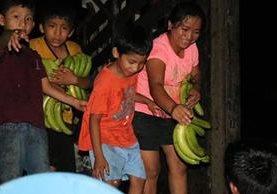Niños y adultos abordaron los camiones para llevar bananos. (Foto Prensa Libre: Cristian I. Soto)