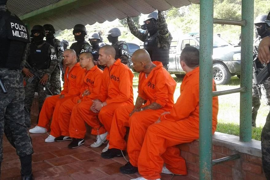Prisioneros, líderes de pandillas criminales, esperan a ser fichados para ingresar a su nueva cárcel. (Foto Prensa Libre. AFP).