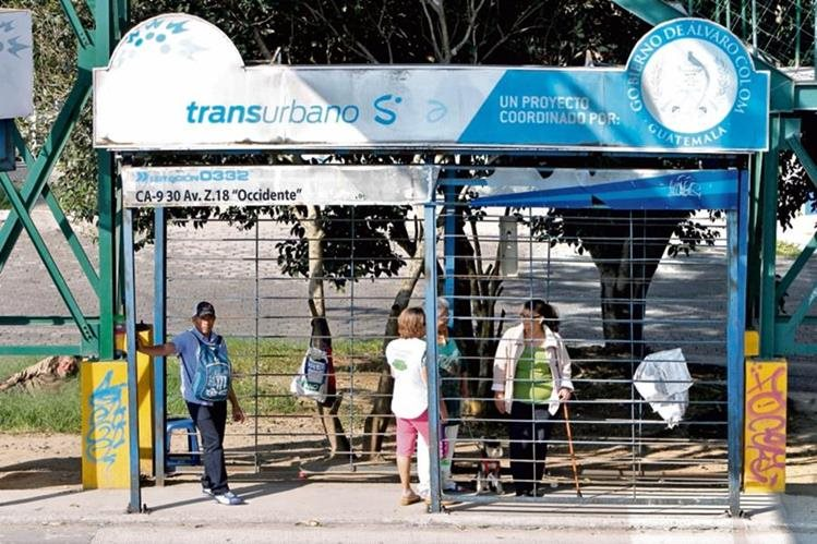 Sin resguardo de agentes de seguridad privada, personas esperan la llegada de un bus en la carretera al Atlántico, zona 18.