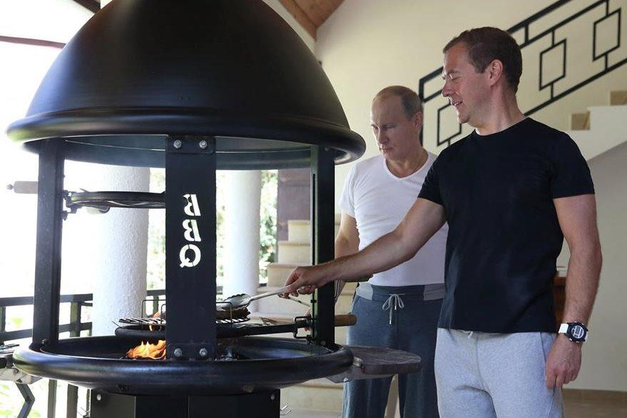 El presidente ruso, Vladimir Putin (izquierda), y su primer ministro Dmitry Medvedev (derecha), cocinan un asado en la residencia del mandatario ruso. (Foto Prensa Libre: EFE).