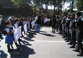 La falta de cinco maestros en la Escuela El Amparo I provocó que los alumnos y sus padres salieran a bloquear el paso el Anillo Periférico. (Foto Prensa Libre: E. Paredes)