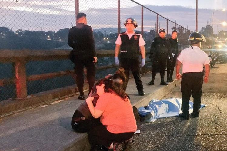 Familiares del presunto delincuente lamentan su muerte en el puente El Incienso, zona 3. (Foto Prensa Libre: Cortesía CVB).