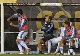 Luis Suárez da un golpe luego de no ingresar al juego. (Foto Prensa Libre: AFP)