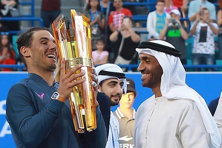 El tenista español Rafael Nadal recibe el trofeo de campeón en Abu Dabi. (Foto Prensa Libre: AP).