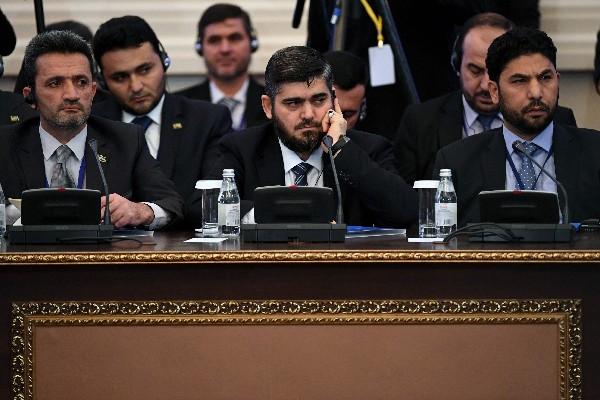 El jefe de la oposición Mohammad Alloush (C) asiste a la primera sesión de conversaciones de paz. (AFP).