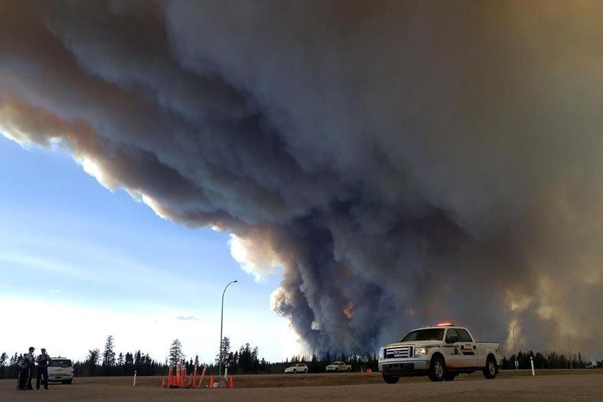 Una enorme columna de humo se observa en la ciudad de Fort McMurray que ha quedado casi sin habitantes debido al grave incendio. (Foto Prensa Libre: AFP).