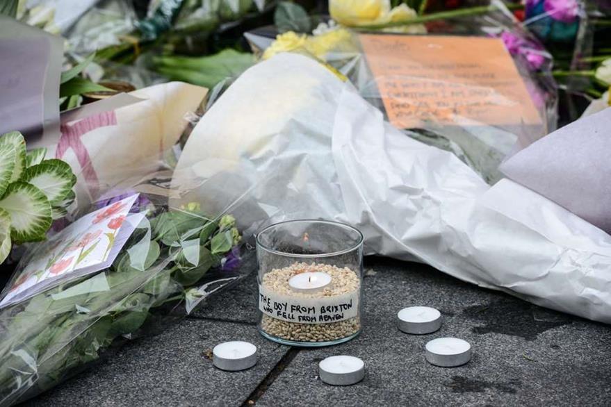 Flores, velas y varios artículos son depositados en un altar en Londres en el que miles de seguidores de Bowie recuerdan su legado. (Foto Prensa Libre: AP)