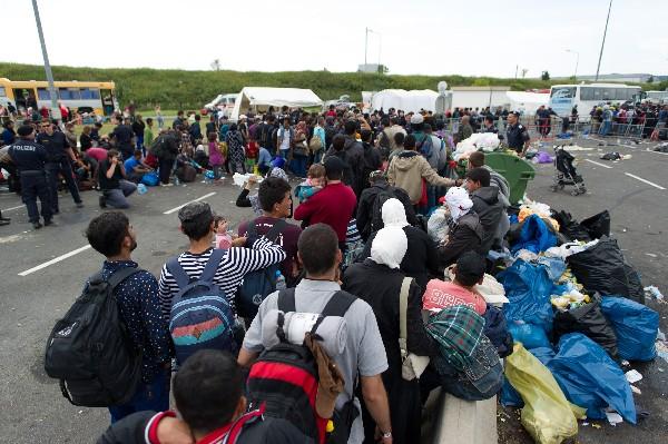 Refugiados esperan los autobuses tras de cruzar la austríaca - frontera húngara.