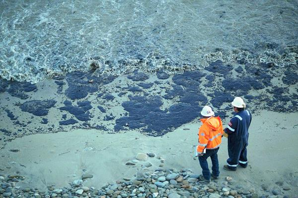 Los funcionarios caminan por una playa cubierta de petróleo al norte de Goleta, California. (Foto Prensa Libre:AP