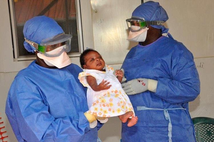 Enfermeros cargan a Nubia, una bebé que fue la última persona infectada con ébola en Guinea y que ya ha sanado. (Foto Prensa Libre: AFP).