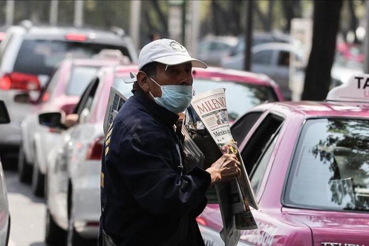 Un vendedor de prensa usa tapabocas como medida por la mala calidad del aire.(EFE).