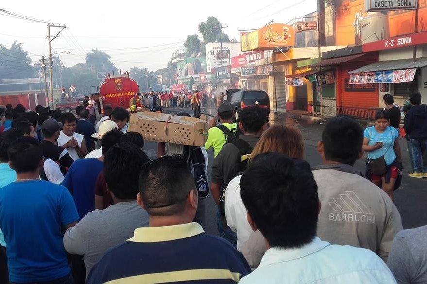 Vecinos de la cabecera de Retalhuleu observan vehículo incendiado. (Foto Prensa Libre: Jorge Tizol)