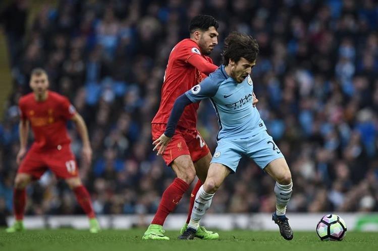 Emre Can trata de quitarle el balón a David Silva. (Foto Prensa Libre: AFP)