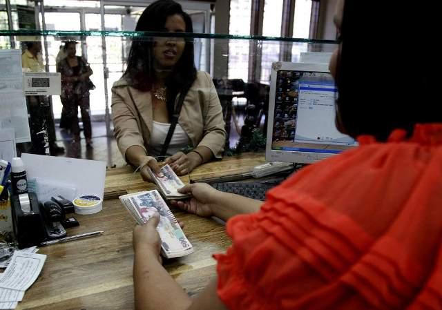 Una joven recibe un envío de remesas en una institución bancaria de La Ceiba, Honduras. (Foto Prensa Libre: laprensa.hn)
