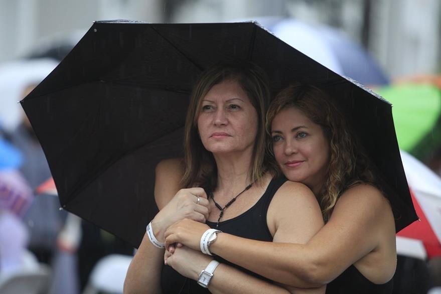 Dos lesbianas presencian la boda masiva de parejas del mismo sexo en Puerto Rico. (Foto Prensa Libre: AP).