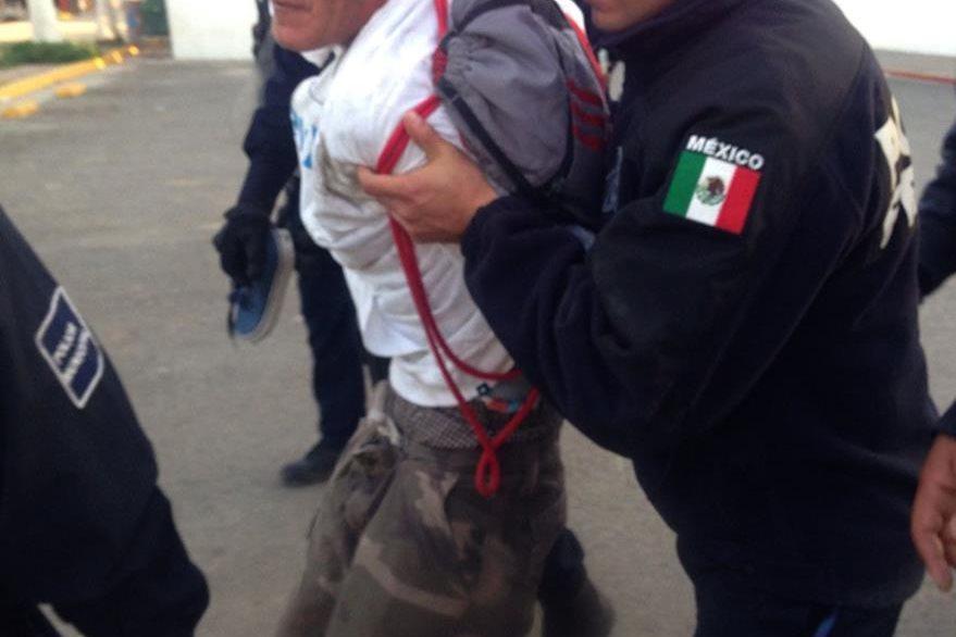 La policía detiene a uno de los revoltosos en Rosarito. (Foto Prensa Libre: EFE)