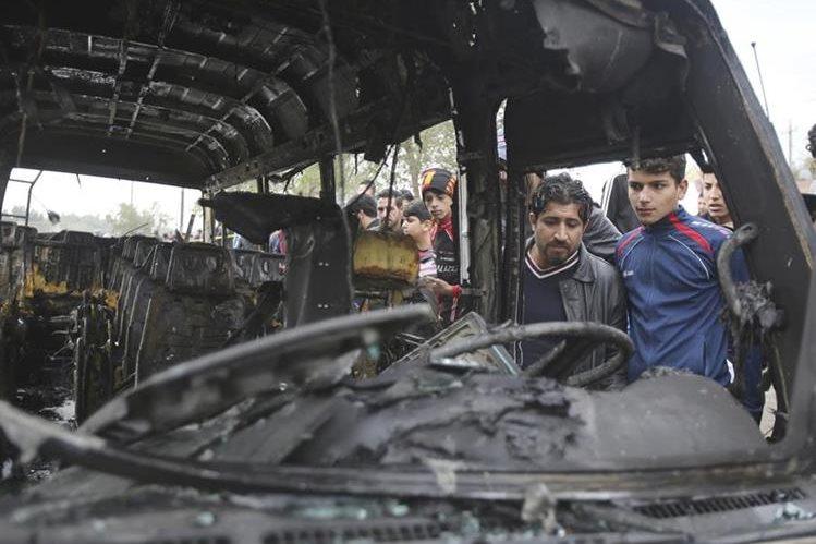 Curiosos observan el interior del microbús en que el atacante perpetró el atentado terrorista en Bagdad. (Foto Prensa Libre: AP).