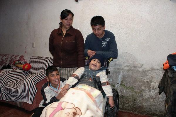 Joshua Yac Ramos, en la silla de ruedas,  acompañado de su familia, en Cantel.