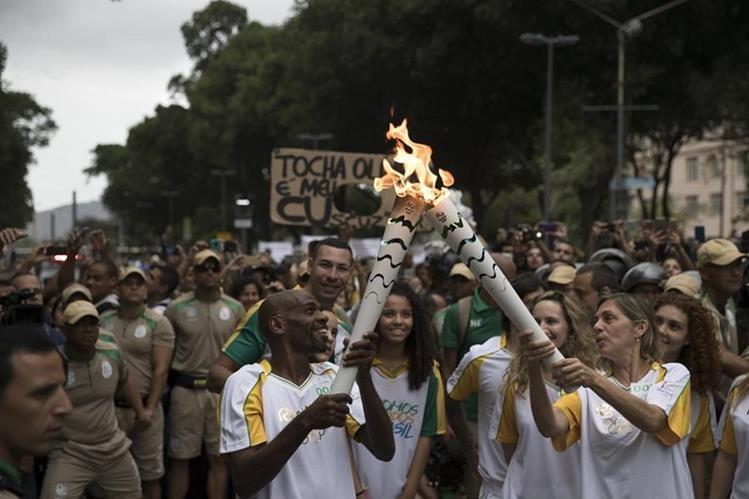Varios artistas brasileños participaron de relevos de la llama olímpica. Renato Sorriso hace el relevo con Carla Camurati. (Foto Prensa Libre: AFP)
