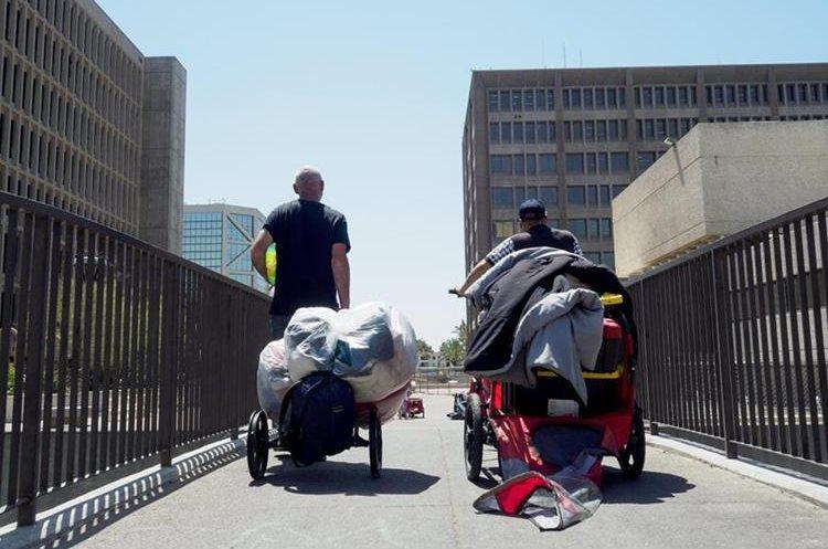 Dos hombres sin techo salen con un carrito con sus pertenencias en el Condado de Orange, California. (EFE).