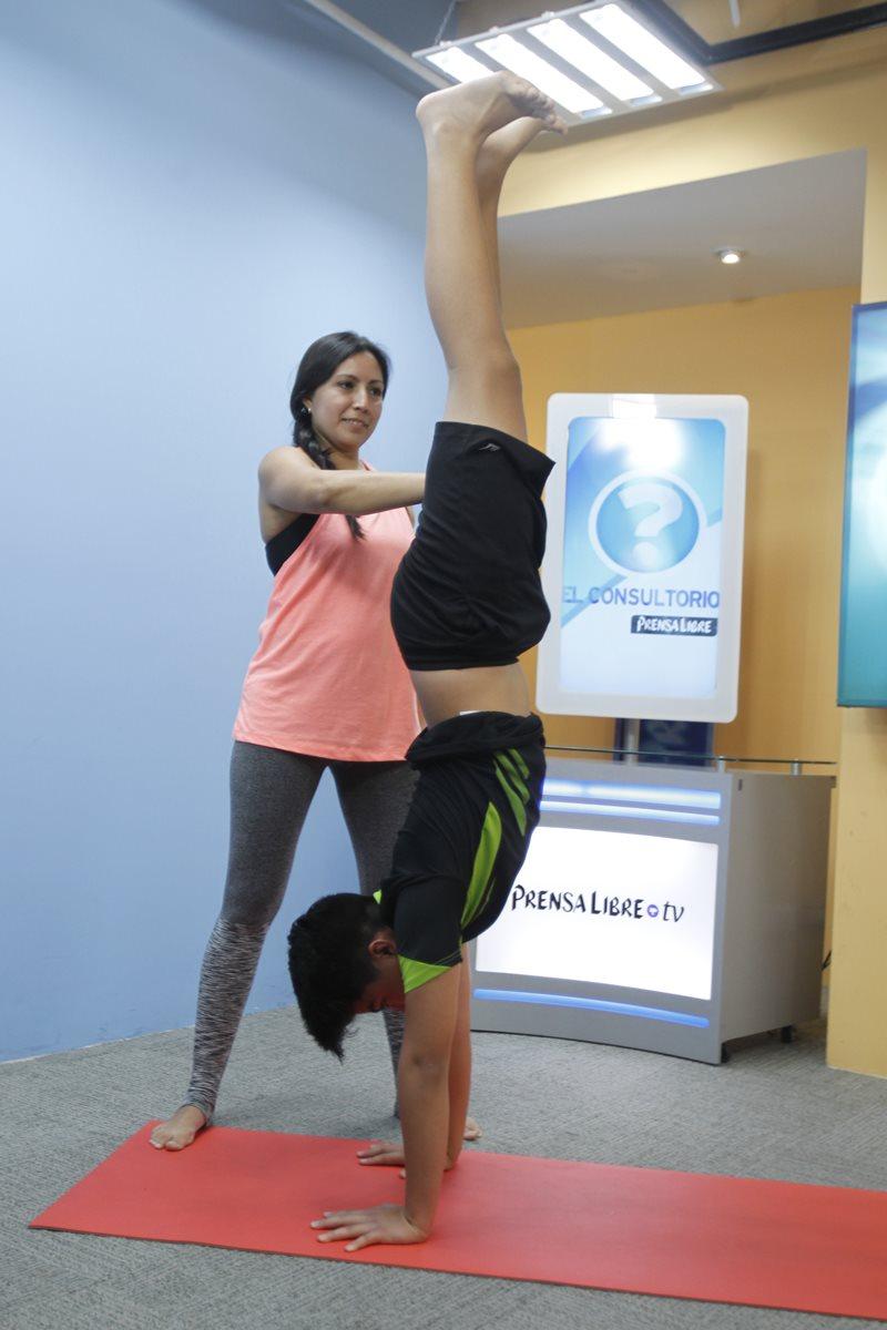 """La instructora de yoga Rossana de León ayuda a Marcelo Hernández a lograr la postura """"handstand"""" con apoyo. Este movimiento fortalece los músculos y estimula la concentración y el equilibrio."""