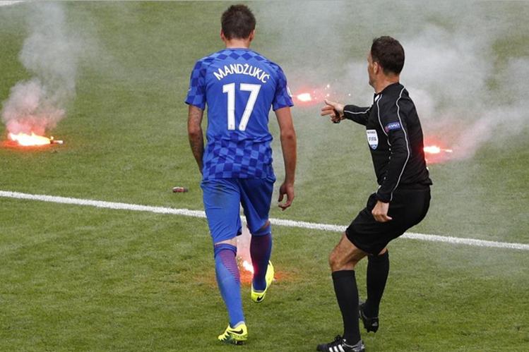 Mario Mandzukic, de Croacia observa como caen las begalas al terreno de juego. (Foto Prensa Libre: EuroSport.com)
