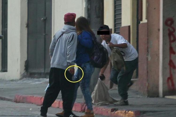 La víctima de asalto intenta alejarse de su agresor que sostiene en la mano derecha un cuchillo. (Foto Prensa Libre)