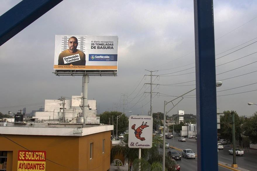 """Valla con la imagen de un ciudadano y el rótulo de """"Detenido por cochino"""", como si fuera delincuente, por arrojar basura en la calle. (Foto Prensa Libre: EFE)."""