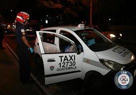 Un socorrista observa el interior del taxi cuyo piloto fue ultimado. (Foto Prensa Libre: Bomberos Municipales).