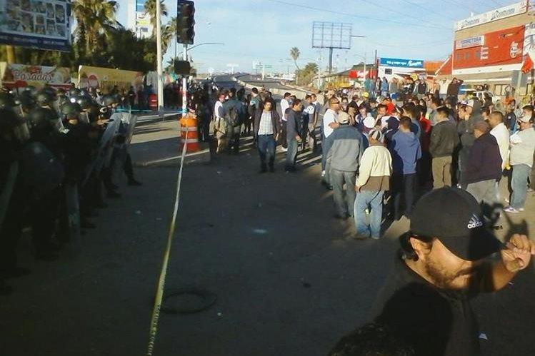 Un grupo de manifestantes durante la protesta en el ingreso a la planta petrolera Pemex de Tijuana. (Foto Prensa Libre: EFE)