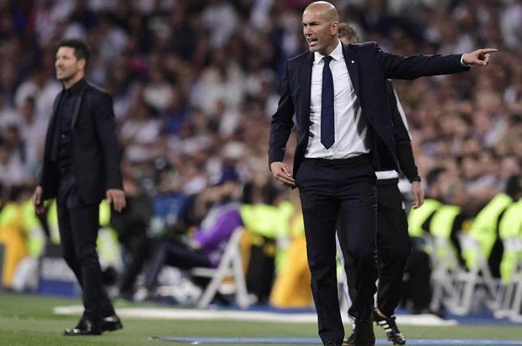 Los técnicos Zinedine Zidane del Real Madrid y Diego Simeone (al fondo) dan instrucciones desde su área técnica.