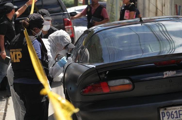 Agentes del MP buscan indicios en este vehículo estacionado a un lado del negocio allanado. (Foto: Erick Avila)