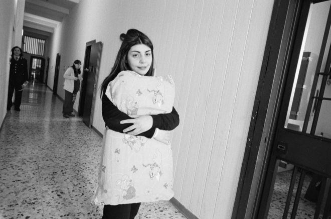 Giampiero Corelli ha fotografiado a las reclusas en Italia. En Nápoles, una mujer lleva su ropa de cama en un pasillo. GIAMPIERO CORELLI