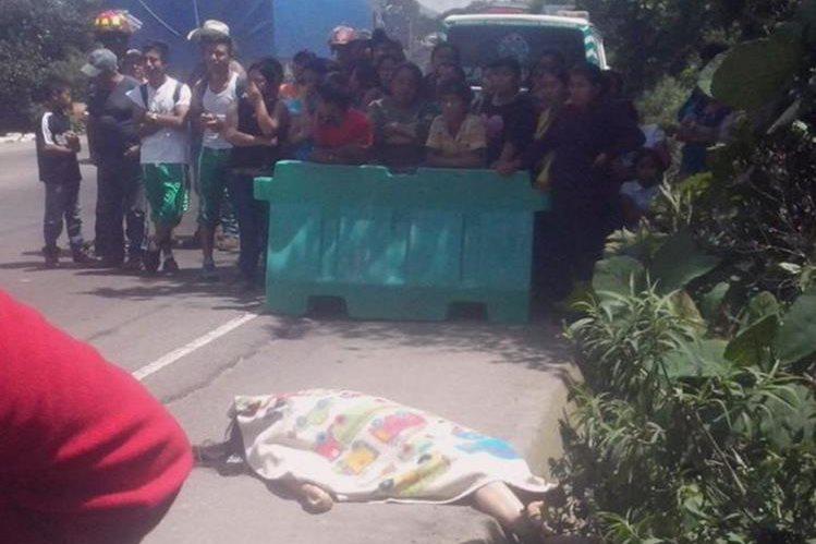 Vecinos observan el cadáver de la mujer que fue arrollada por un camión en el kilómetro 60 de la rua Interamericana. (Foto Prensa Libre: José Rosales)